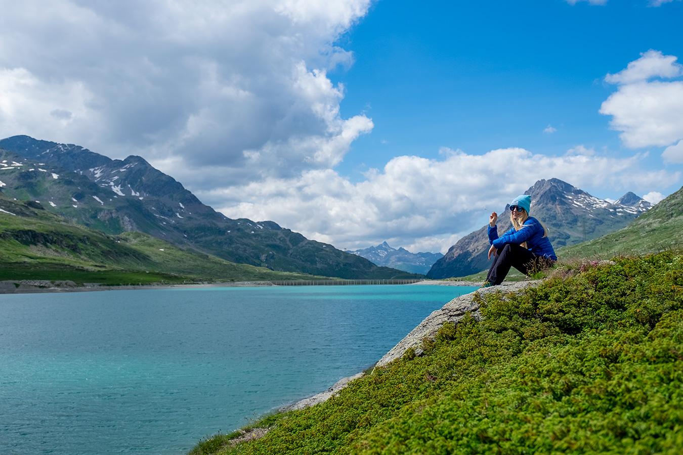 dziewczyna w niebieskim ubraniu siedząca nad brzegiem turkusowego górskiego jeziora